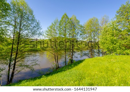 The lake is a large body of water surrounded by land. Walnut and pine trees grow along the edge, complete calm, beautiful hatching in the water #1644131947