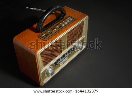 Retro old radio receiver with copy space on table on black background #1644132379