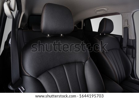 the interior of the car is covered with handmade genuine leather. front car seats. top. head restraints and seat belts are visible. High-quality stitching with gold threads and skin texture are visibl Royalty-Free Stock Photo #1644195703