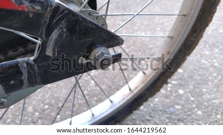 Bicycle Wheel Steel spokes and central wheel mount to the bike frame close-up. Nut on the bolt. Metal parts are qualitatively assembled into a product. Clay and dirt adhered to the rubber tire #1644219562