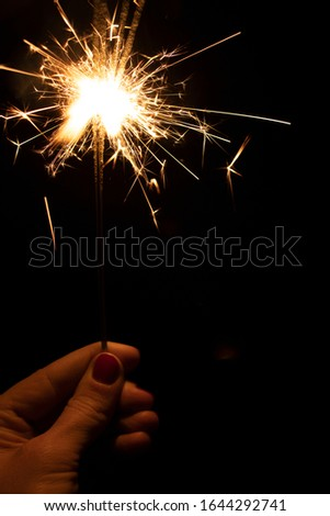 Sparklers in the dark. Sparks with fire in hands on a stick. #1644292741