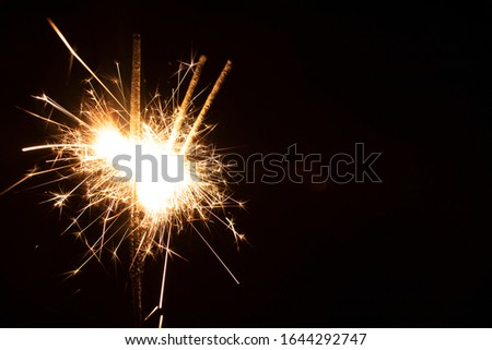 Sparklers in the dark. Sparks with fire in hands on a stick. #1644292747