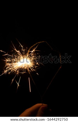 Sparklers in the dark. Sparks with fire in hands on a stick. #1644292750