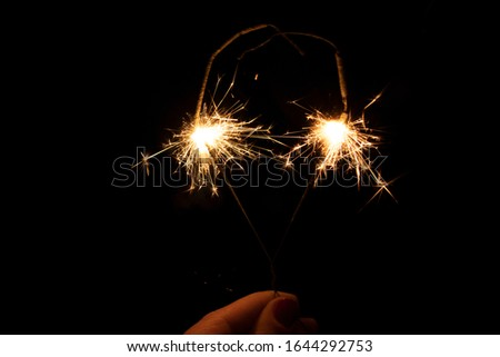 Sparklers in the dark. Sparks with fire in hands on a stick. #1644292753