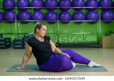 Overweight woman overweight doing fitness with ball. Obese blonde is resting after a productive workout in the gym. #1644357649