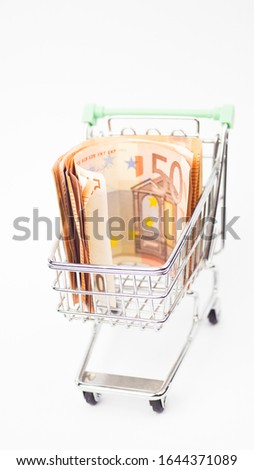 The concept of buying currency. Buying Euros. Metal cart with euro banknotes on a white background. close up. #1644371089