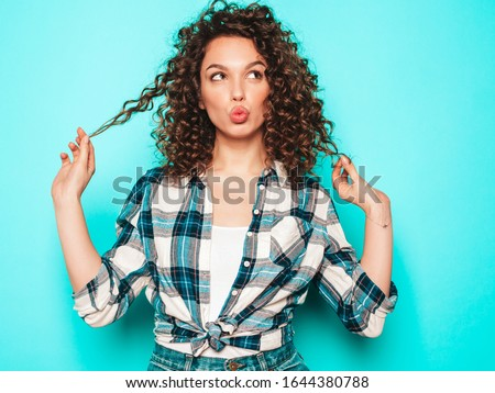 Portrait of beautiful smiling model with afro curls hairstyle dressed in summer hipster clothes.Sexy carefree girl posing in studio near blue wall.Trendy funny and positive woman #1644380788
