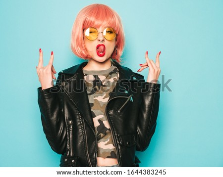 Young beautiful hipster bad girl in black leather jacket and earring in nose.Sexy carefree  woman posing in studio in pink wig near blue wall.Confident model in sunglasses.Shows rock and roll sign #1644383245