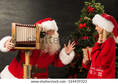 Photo of Santa Claus with his wife taking pictures with Christmas gift at home