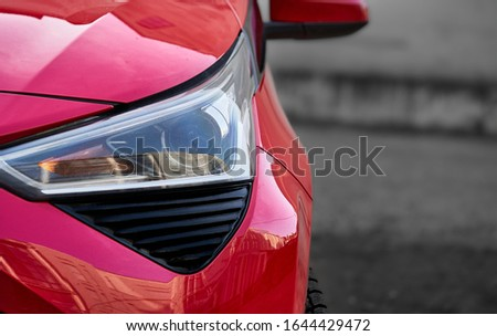 Headlights and hood of sport red car with silver stars Royalty-Free Stock Photo #1644429472