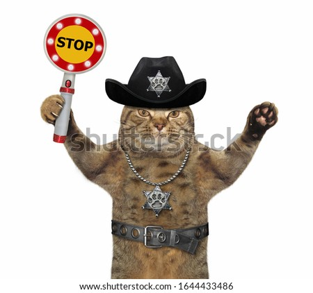 The beige cat policeman is wearing in a black cowboy hat, a police badge around his neck and a stainless steel belt. He holds a stop sign. White background. Isolated.