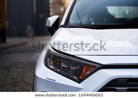 Headlights and hood of sport white car with silver stars Royalty-Free Stock Photo #1644466063
