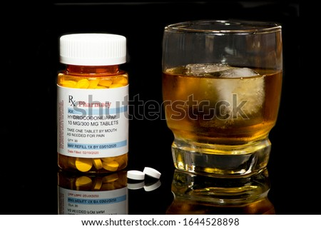 Tumbler of alcoholic beverage and ice with hydrocodone/APAP prescription bottle and white prescription medication tablets. Mixing drugs and alcohol concept. #1644528898