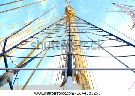 Ratlines (lines used to climb up the mast), mast and rigging of a classic sailing ship. #1644583255
