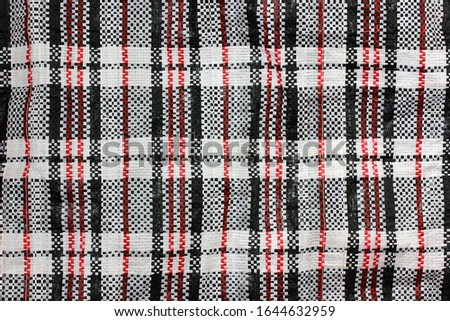 checkered bag. texture of Chinese plastic braided material in black, white and red colors. background, striped backdrop.