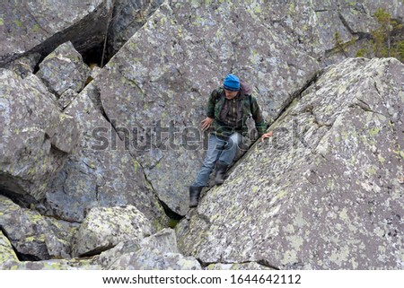 Southern Urals. A mature tourist makes an ascent to the top along a large stone placer. #1644642112