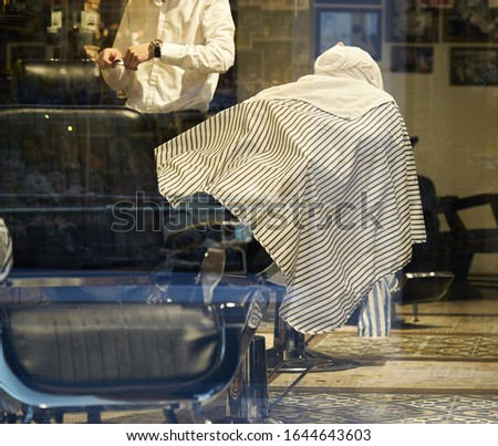Rear view shot of handsome hairdresser cutting hair of male client. Hairstylist serving client at barber shop Royalty-Free Stock Photo #1644643603