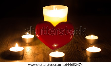 Christmas divination. Fortune telling. Divination for love. The red heart stands in the middle of the lighted candles. Ritual of love spell of the person. Postcard for Valentine's day or women's day Royalty-Free Stock Photo #1644652474