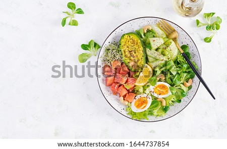 Ketogenic diet breakfast. Salt salmon salad with greens, cucumbers, eggs and avocado. Keto/paleo lunch. Top view, overhead Royalty-Free Stock Photo #1644737854