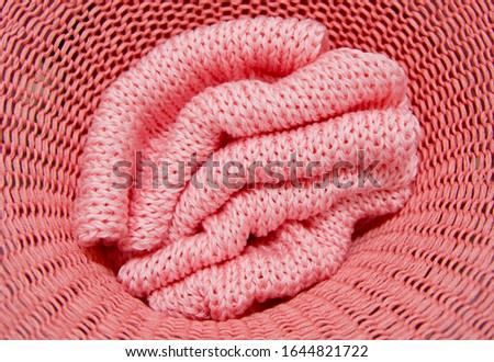 Knitted from a two shade pink yarn sweater and thread for knitting closeup. Knitting as a hobby. Accessories for knitting. #1644821722