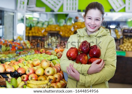 Glad preteen girl standing near shelves with fruits in greengrocery, holding ripe red apples #1644854956