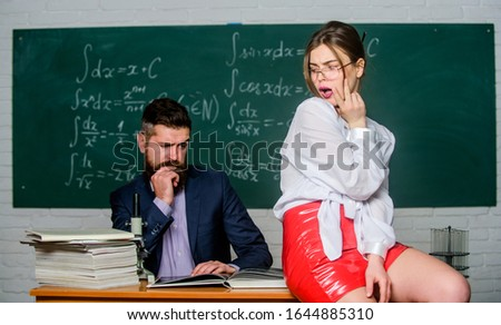 Distracting him from work. Private lesson. Check knowledge. Desire for knowledge. Sex knowledge. Need for real experience. Teacher and student in classroom chalkboard background. Sexy seduction. #1644885310