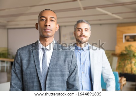 Two confident businessmen looking at camera. Concentrated young men wearing formal wear posing in office. Business, confidence concept #1644891805