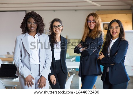 Group of confident young women looking at camera. Beautiful smiling businesswomen posing in modern office. Female confidence concept #1644892480