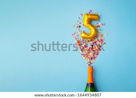 5th anniversary champagne bottle balloon pop Royalty-Free Stock Photo #1644934807