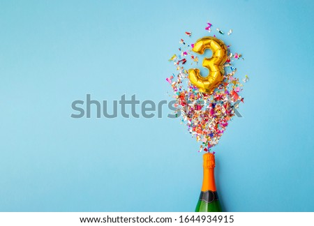 3rd anniversary champagne bottle balloon pop Royalty-Free Stock Photo #1644934915