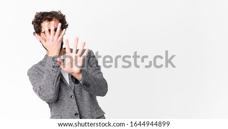 young crazy businessman covering face with hand and putting other hand up front to stop camera, refusing photos or pictures against flat wall