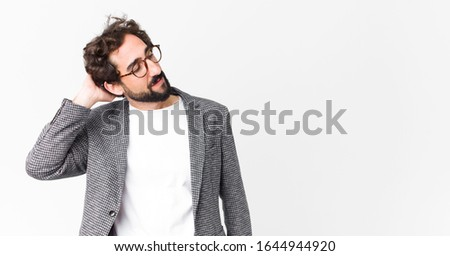 young crazy businessman smiling cheerfully and casually, taking hand to head with a positive, happy and confident look against flat wall #1644944920