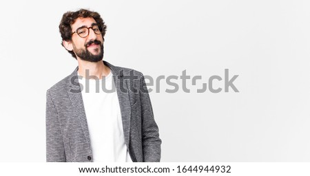 young crazy businessman smiling cheerfully and casually with a positive, happy, confident and relaxed expression against flat wall #1644944932