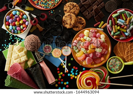 Selection of party treats for a kids birthday with assorted candies, ice cream , cookies, biscuits, chocolate bars, sprinkles and lollipops in an overhead view Royalty-Free Stock Photo #1644963094