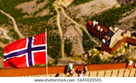 Trollstigen mountain road landscape in Norway, Europe. Norwegian flag waving and many tourists people on viewing platform in background. National tourist route. #1645020505