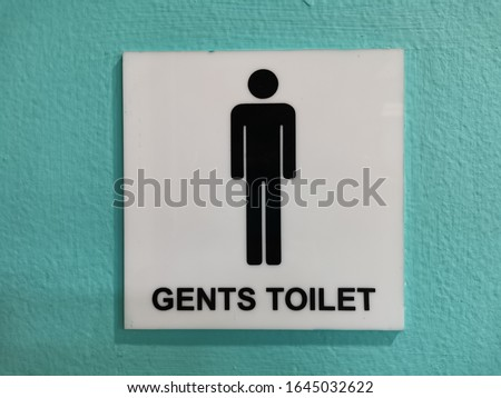 Signs of male and female toilets with a green walls background