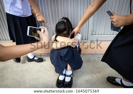 Problems of bullying at school,sad stressed asian girl student crying sitting on the floor,group of hands pointing finger to scared schoolgirl, bullying victim being video recorded on a mobile phone #1645075369