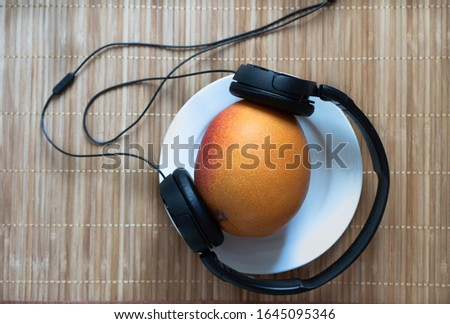 ripe orange ripe mango in black headphones on a white plate on a wooden background #1645095346