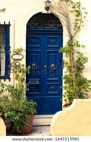Vertical picture of traditional stone entrance to typical maltese house with blue wooden door and green plants around in Sliema, Malta. Island Malta popular travel destination.