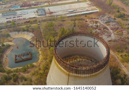 Drone flies over cooling tower near Chernobyl nuclear power plant. Chernobyl nuclear power plant. Cooling tower overlooking the nuclear power plant in Chernobyl. Investigation of cooling tower state. #1645140052