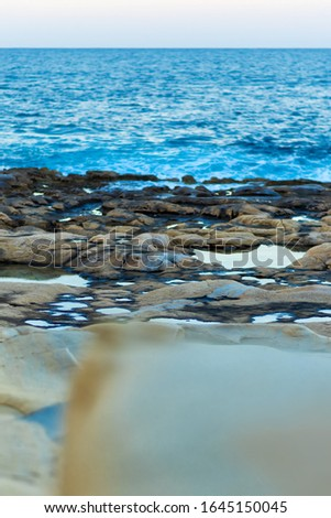 Vertical close-up picture of stone coastline with blue sea and sky in evening. Maltese coast in Sliema, Malta. Tranquille sea ocean landscape. Water and stona natural background.