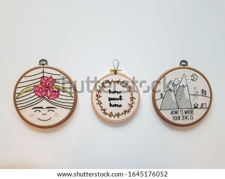Handmade embroidery needlework art on wooden embroidery hoop with neutral background Royalty-Free Stock Photo #1645176052