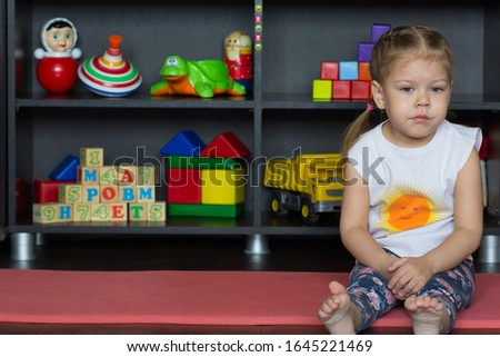 Sad and serious little girl sitting on ground at corner of picture with copy space indoor