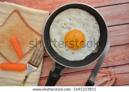 egg cooked in a pan breakfast food on wooden background #1645223815
