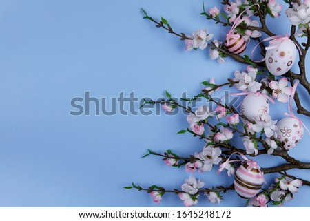 Easter background. Flat lay. On a blue background on the right, branches of a blossoming apple tree decorated with pink Easter eggs. Close-up, horizontal, cropped shot, free space on the left.