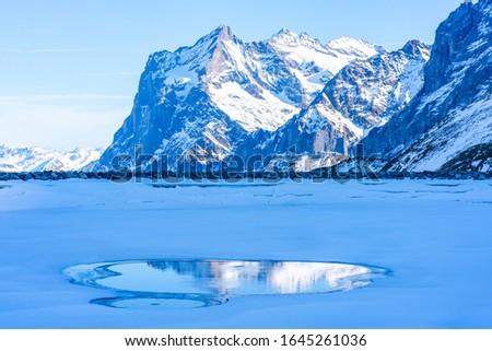 Winter landscape with snow covered peaks and frozen lake on Kleine Scheidegg mountain in Swiss Alps in Grindelwald ski resort, Switzerland #1645261036