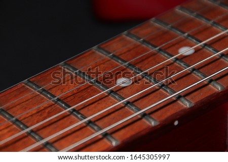 macro of the fretboard of an electric guitar with frets inlays and strings, shadows are below the strings #1645305997
