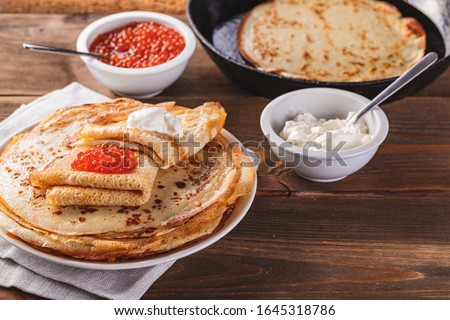 Traditional Russian Crepes Blini stacked in plate and cast-iron frying pan with red caviar, fresh sour cream on dark wooden table. Russian festival meal Maslenitsa or Shrovetide. Royalty-Free Stock Photo #1645318786