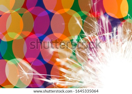 Close-up of colored circles and bright orange fire from a burning candle or salute glows in the dark. New Year and Christmas celebration concept. Birthday concept. Copyspace #1645335064