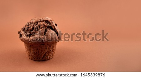 Chocolate muffin stock images. Chocolate muffin isolated on a brown background with copy space for text. One delicious muffin stock images. Chocolate muffin frame #1645339876